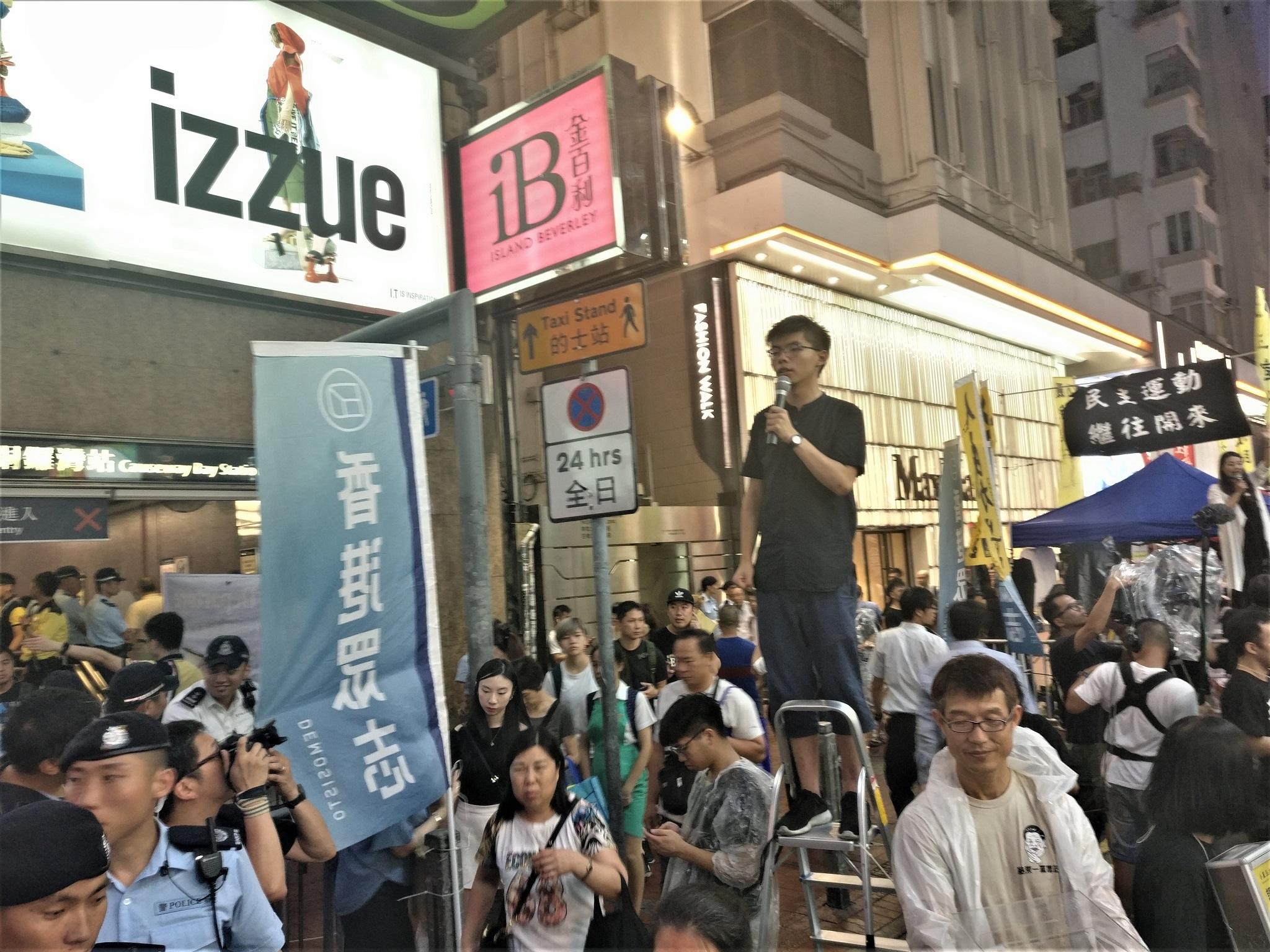 L'activista prodemocràcia Joshua Wong fent un discurs en un carrer adjacent al parc Victòria moments abans de l'inici de l'acte commemoratiu