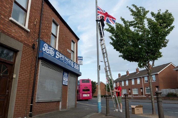 Dos homes pengen la bandera britànica a un barri unionista de l'est de Belfast. Les setmanes prèvies a la marxa Orange del 12 de juliol, es multiplica la simbologia nacional (i també la sectària). / Alfons Cabrera